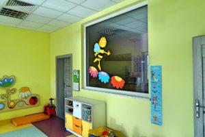 Wewnętrzne pzredszklenie pomiedzy salą a korytarzem. Widonzce szafki oraz drzwi wyjściowe z sali na korytarz