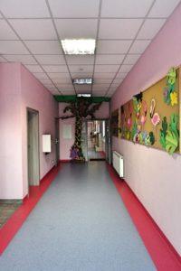 """Prostopadłe ujęcie na przedście pomiedzy wewnetrznymi korytarzami ozdobione wizerunkiem drzewa. Widoczna nablica z napisem """"Koło plastyczne"""" oraz dwie inne yablice ozdobione flamingami i motywami roślinnymi"""