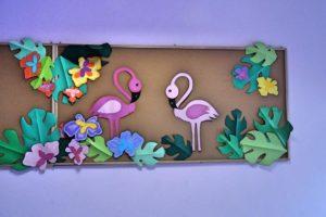 Wisząca na ścianie tablica korkowa ozdobiiona flamingami i motywami roślinnymi