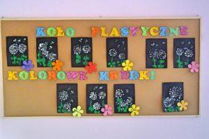 """Wisząca na ścianie tablica korkowa z powieszonymi obrazkami oraz napisem """"koło plastyczne - kolorowe kredki"""""""
