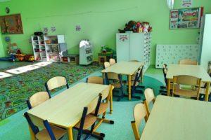 Inne ujęcie wnętrza sali. Na pierwszym planie stoliki dla dzieci, w tle dywan, szafki na zabawki