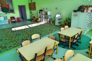 Wnętrze sali. Na pierwszym planie stoliki dla dzieci, w tle dywan, szafki na zabawki oraz drzwi wyjściowe