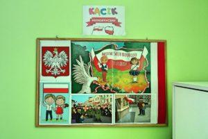"""Tablica ścienna z tytule """"Kącik patriotyczny"""" zawierająca obrazy godła polski, oraz dzieci z flagami Polski"""