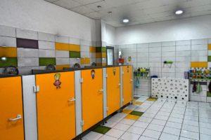 Wnętrze sanitariatów dla dzieci przedstawiające szereg kabin z toaletami