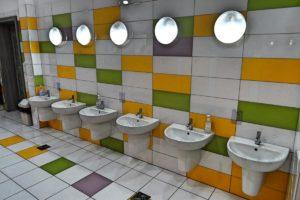 Wnętrze sanitariatów dla dzieci przedstawiajace szereg umywalek