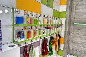 Wnętrze sanitariatów dla dzieci przedstawiające półki z kubkami i szczoteczkami do zebów oraz wieszaki na ręczniki
