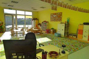 Wnetrze sali pzredszkolnej. Na pierwszym planie biurko, w tle wnętrze z zabawkami i półkami na zabawki a wtle stoliki dla dzieci oraz okno z widokiem na plac zabaw