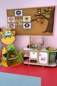 Kącik z półkami z zabawkami oraz tablica dydaktyczna
