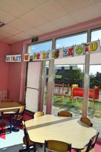 """Wnętrze sali przedszkolenj z wiszącym transparentem o treści """"witamy w przedszkolu"""""""