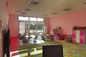 Wnętrze sali przedszkolej. Na pierwszym planie monitor komputera, w środkustoliki i półki z zabawkami, a tle okno z widokiem na plac zabaw