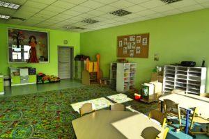 Wnętrze sali przedszkolej - na pierwszym planie stoliki z krzesełkami.