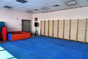 Wnetrze sali gimnastycznej zmatami oraz drabinkami do ćwiczeń