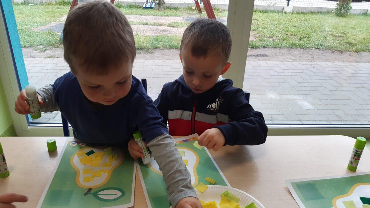 Staś i Karolek wyklejają kawałkami bibuły szablon gruszki