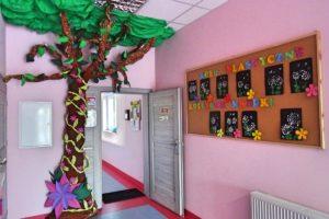 """Przejście pomiedzy wewnetrznymi korytarzami ozdobione wizerunkiem drzewa. Widoczna nablica z napisem """"Koło plastyczne"""""""