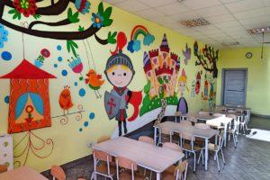 Inne ujęcie wnętrza sali. Na pierwszym planie stoliki, w tle ściana ozdobiona rysunkami
