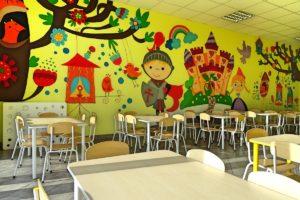 Wnętrze sali. Na pierwszym planie stoliki, w tle ściana ozdobiona rysunkami