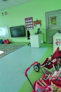 Wnetrze sali przedszkolnej. Na pierwszym planie wóżki dla lalek, w tle biurko i wiszący na ścianie telewizor