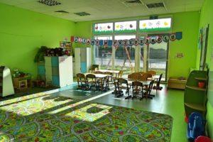 Wnetrze sali. Na pierwszym planie dywan, w tle stoliki dla dzieci oraz okno z widokiem na plac zabaw
