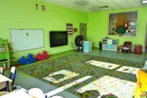Wnętrze sali przedszkolej. Na głównym planie dywan do zabaw a w tle tablica dydaktyczna, telewizor, biurko oraz szafka na materiały dydaktyczne