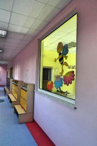 Korytarz przedszkola z szatnią oraz przeszkleniem między korytarzem a salą
