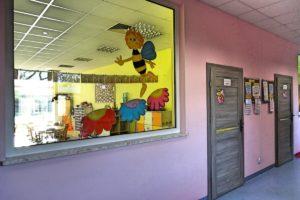 Korytarz przedszkola z drzwiami do sali oraz przeszkleniem między korytarzem a salą