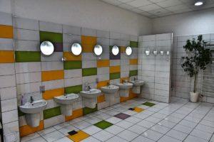 Inne ujęcie sanitariatów dla dzieci przedstawiajace szereg umywalek