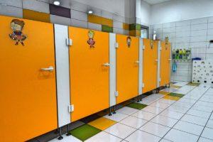 Inne ujęcie wnętrza sanitariatów dla dzieci przedstawiające szereg kabin z toaletami