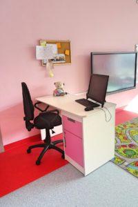 biurko wychowawcy z fotelem i laptopem - w tle telewizor wiszący na ścianie