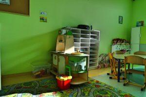 Kącik z regałami i półkami z zabawkami w sali przedszkolej
