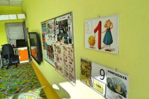 Ściana sali przedszkolen z widocznymi materiałami dydaktycznymi oraz telewizorem