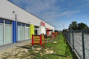 Plac zabaw na terenie przedszkola z widoczną ścianą frontową