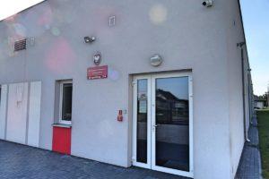 Drzwi wejściowe do budynku Przedszkola z tablicą informacyjną